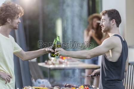 two men clinking beer bottles at