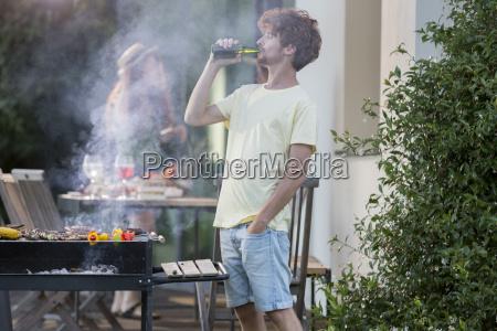 man having a beer at barbecue