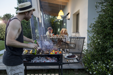 man at barbecue grill with friends