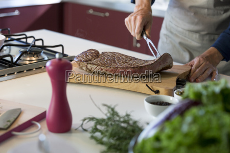 young man cutting grilled teak at