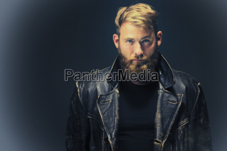 man with leather jacket against dark