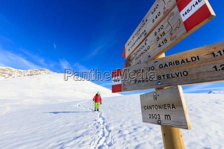 hiker with snowshoe proceeds on the
