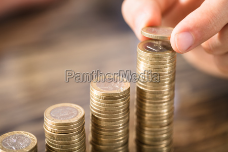 person placing coin over the coins