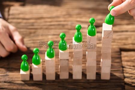 businessman, arranging, the, figures, on, block - 22695605