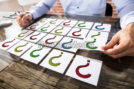 businessman, holding, question, mark, on, adhesive - 22695697