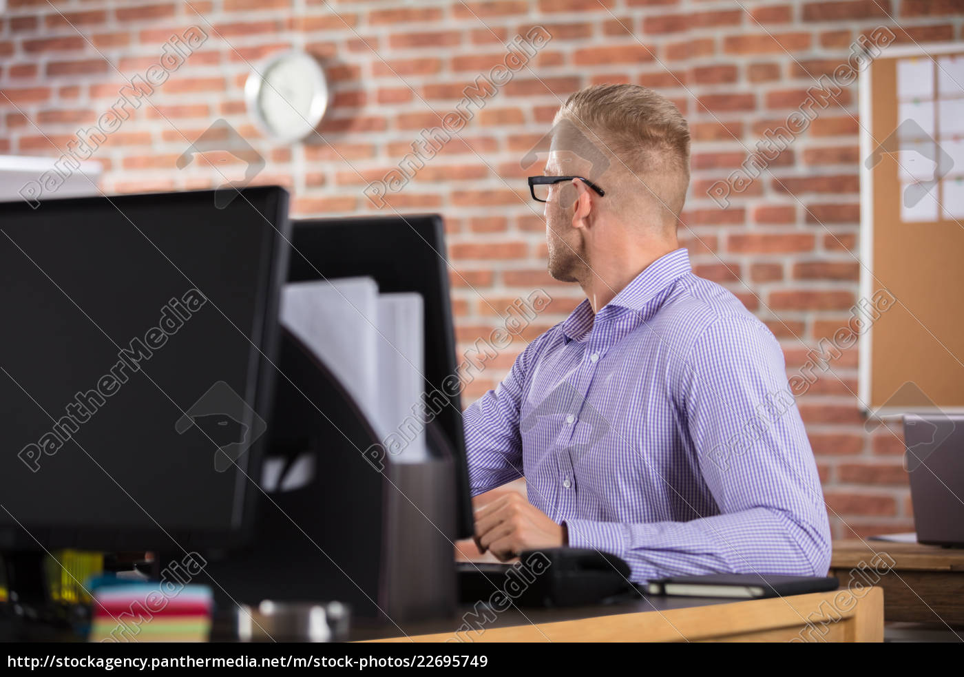 businessman, looking, at, clock, in, office - 22695749
