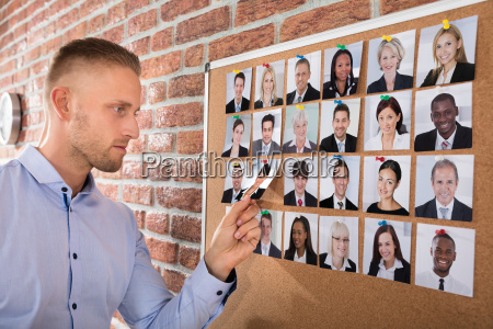 businessman, selecting, candidates, photo, on, corkboard - 22695689