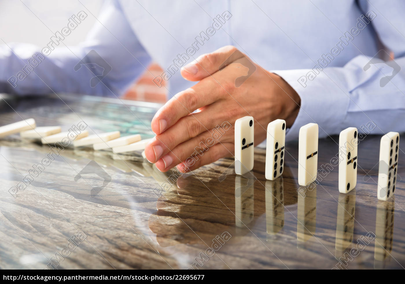 businessman, stop, dominoes, on, desk - 22695677