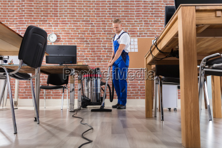 janitor, cleaning, floor, with, vacuum, cleaner - 22695735