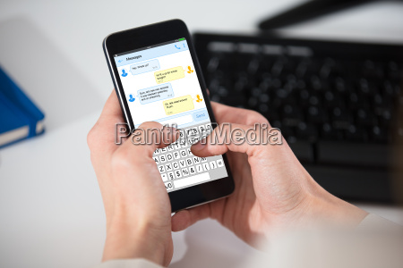 person sending messages on cell phone