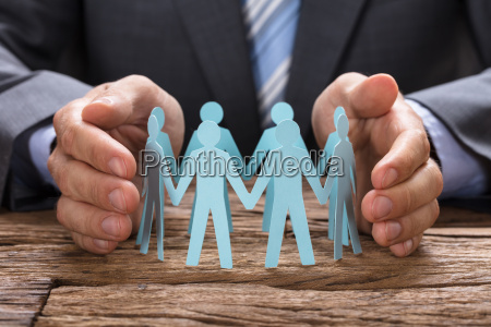 businessman covering paper team with hands