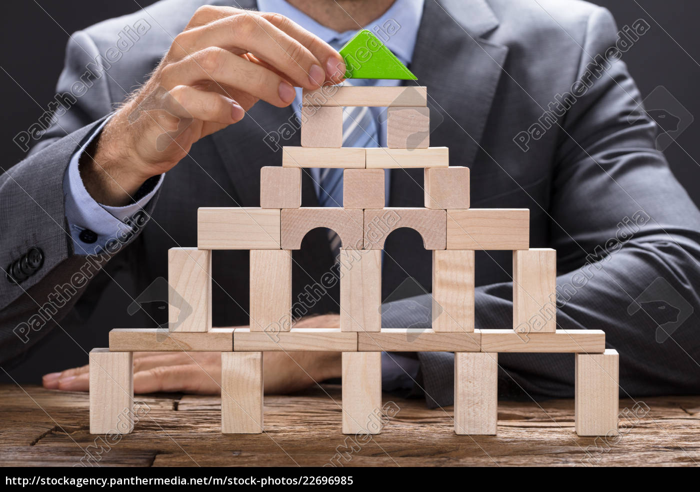 businessman, making, building, with, wooden, blocks - 22696985