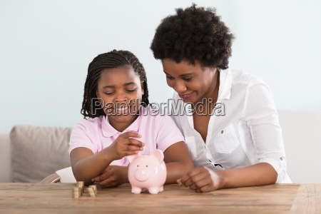 girl, with, mother, inserting, coins, in - 22696115