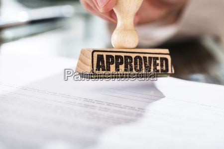 person, holding, approved, stamp, on, document - 22696661