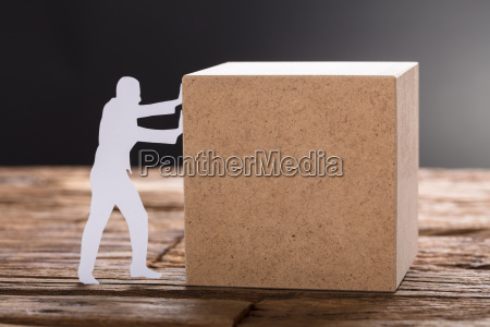 paper man pushing wooden block on