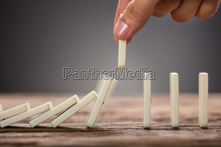 businessman, picking, domino, piece, on, wooden - 22697043