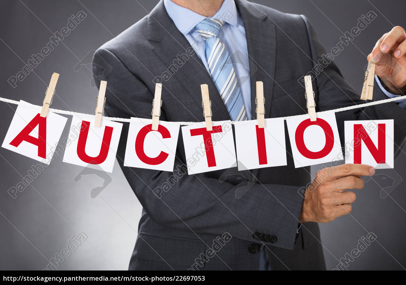 businessman, pinning, auction, cards, on, clothesline - 22697053