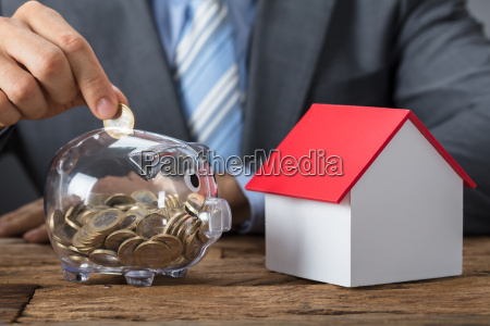 businessman, putting, coin, into, piggybank, by - 22697075