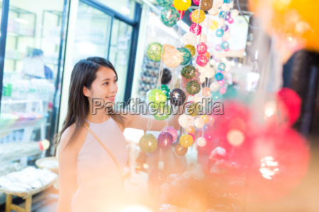 young woman shopping in lamp store