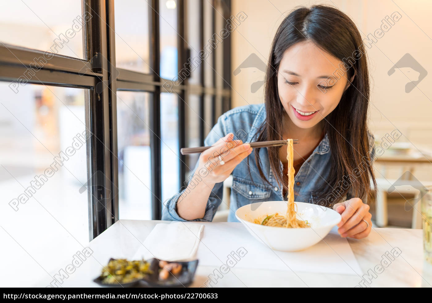 woman, eating, noodles, in, chinese, restaurant - 22700633