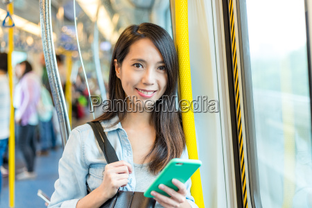woman, holding, cellphone, on, train - 22700653