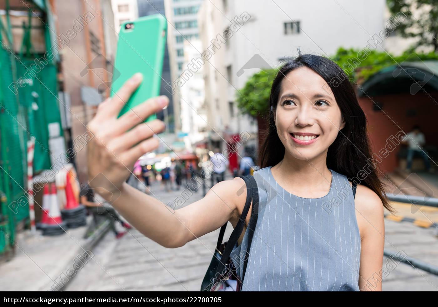 woman, taking, selfie, in, pottinger, street - 22700705