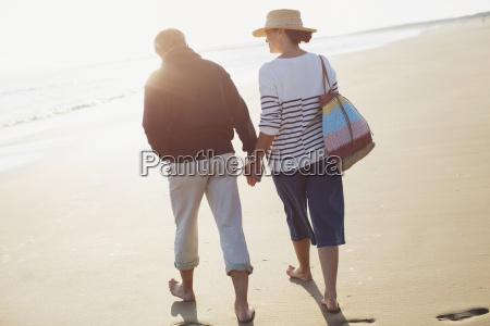 barefoot mature couple holding hands and