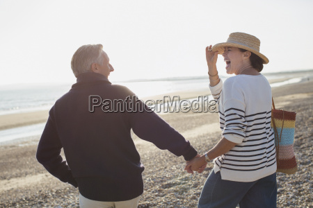 laughing mature couple holding hands and