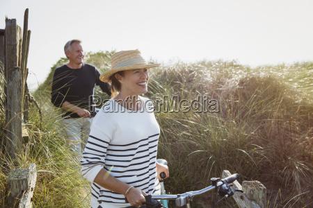 mature couple walking bicycles along sunny