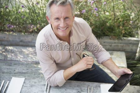 portrait smiling senior man using digital