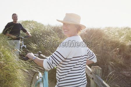 portrait smiling mature woman walking bicycle
