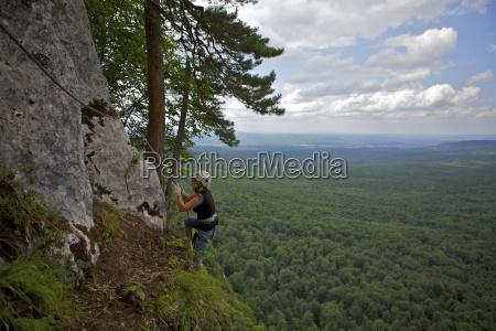 woman climbing cliff via ferrata guam