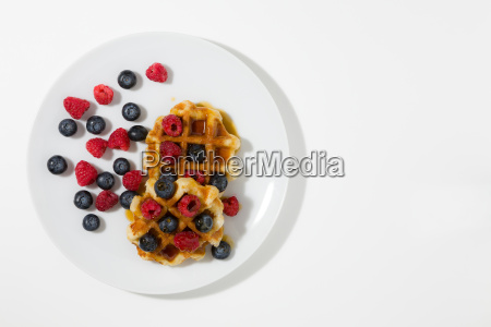 waffles with berries and maple syrup