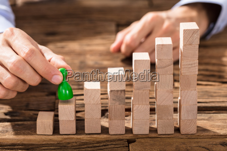 businessman placing the green figure on