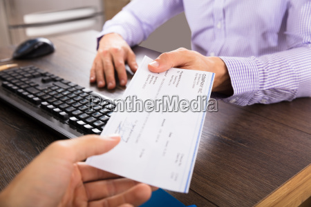 businessman giving cheque to her colleague