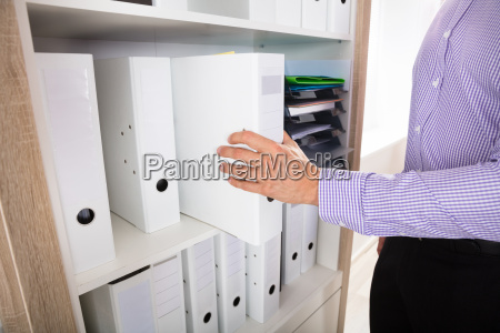 person's, hand, taking, folder, from, shelf - 22721413