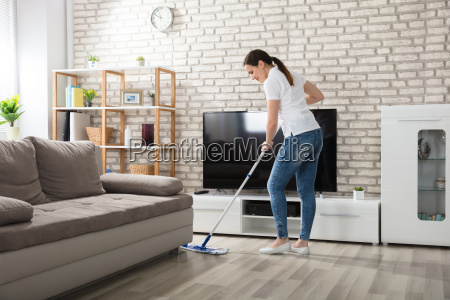 young woman cleaning the hardwood floor