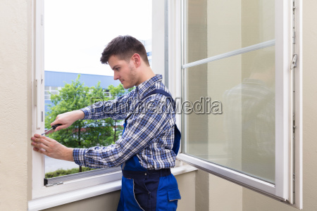 repairman fixing window with screwdriver