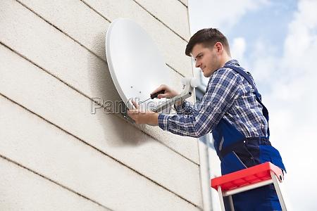 technician installing tv satellite dish on