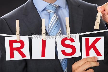 businessman, pinning, risk, cards, on, clothesline - 22722365