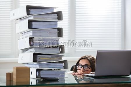 businesswoman, peering, the, folders, stack, in - 22722111