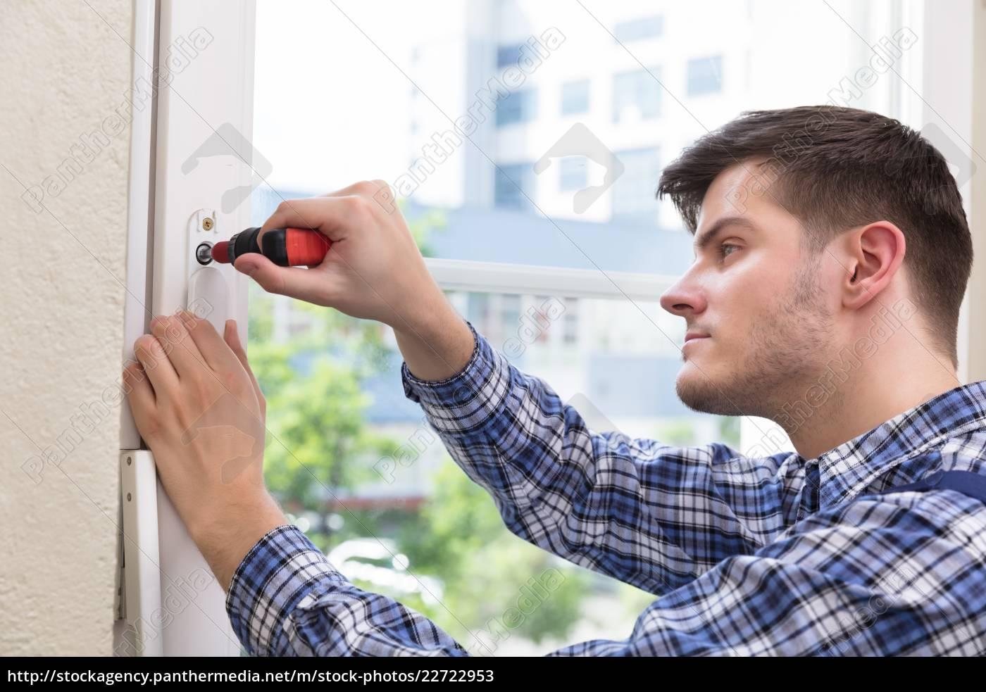 handyman, fixing, window, with, screwdriver - 22722953