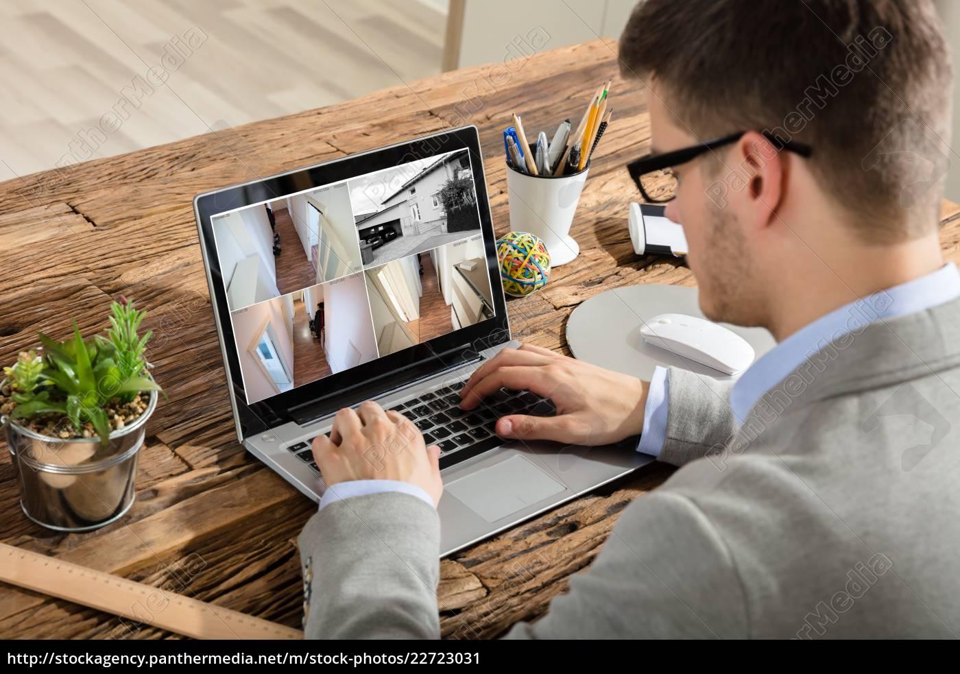 businessman, checking, cctv, footage, on, laptop - 22723031