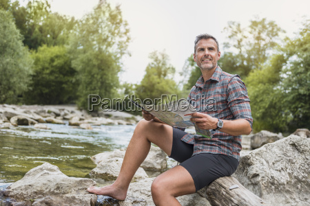 hiker sitting at riverbank with map