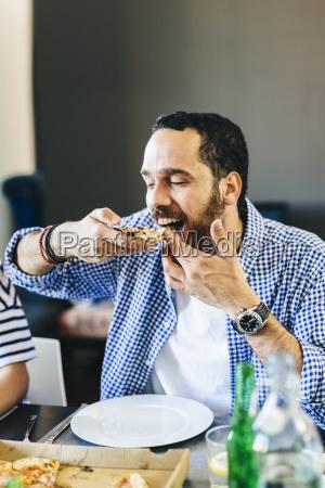 young man enjoying slice of pizza