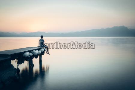 italy lazise man sitting on jetty