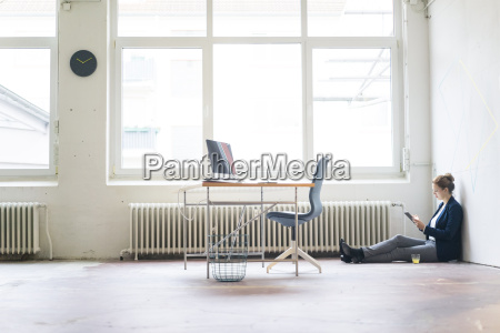 businesswoman sitting on floor in office