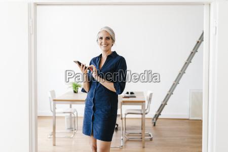 businesswoman sitting on windiwsill