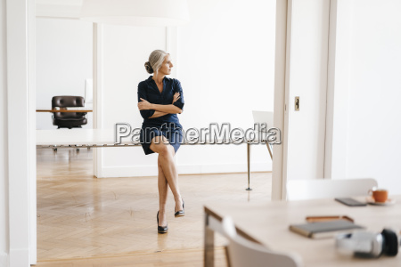 businesswoman sitting on table in modern