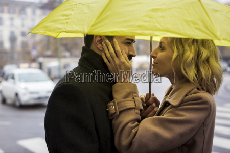 affectionate business couple under umbrella in